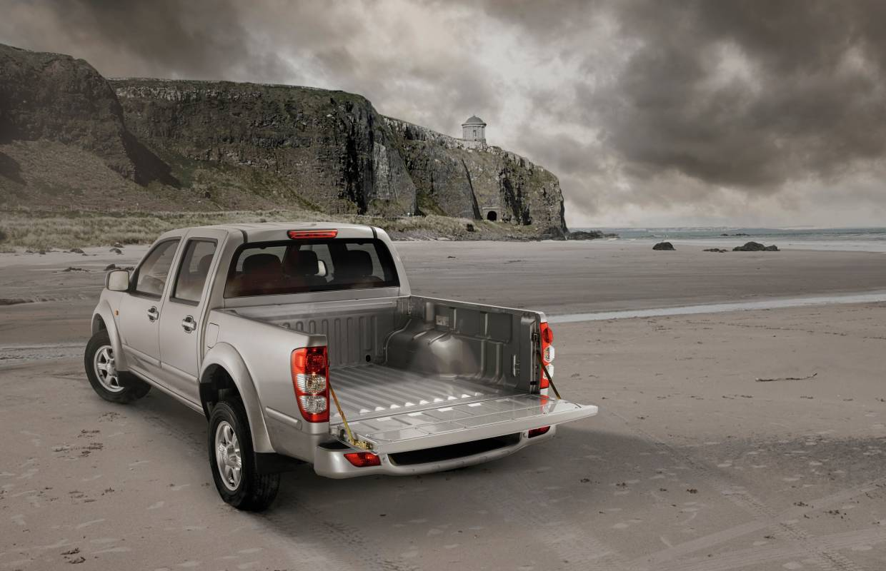 Silver pick-up truck on beach