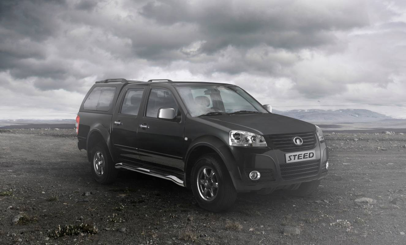 Black and white image of car with landscape and clouds