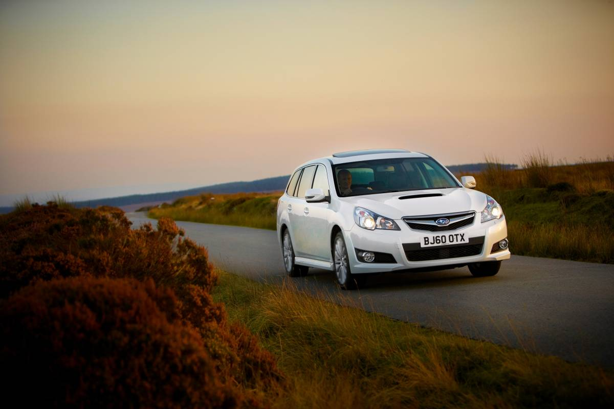 White car with sunroof in sunset on moors