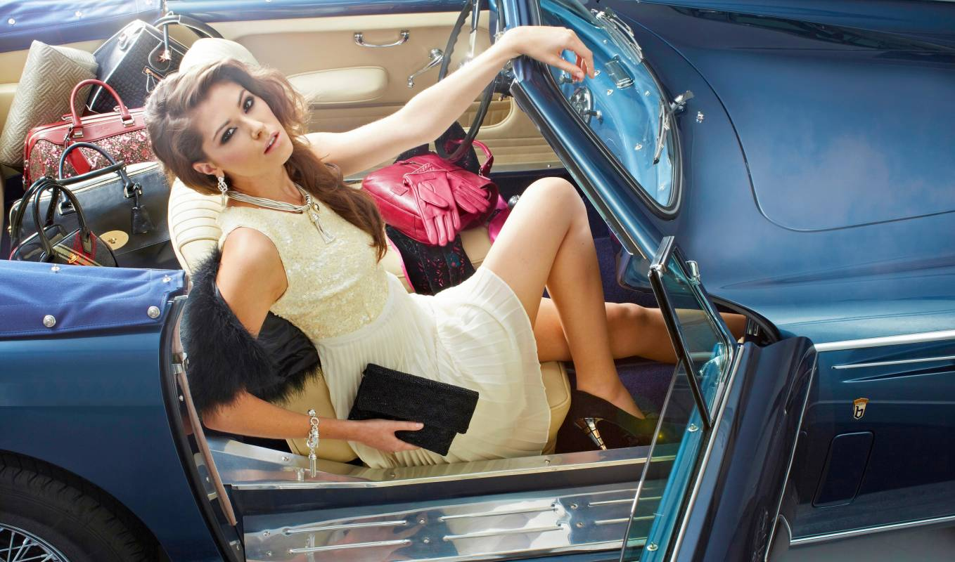 City girl in blue convertible car with sequin top and pleated skirt with designer handbags