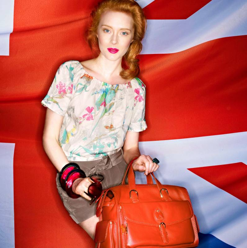 Beautiful red haired model with red leather handbag and velour shorts for catalogue shot