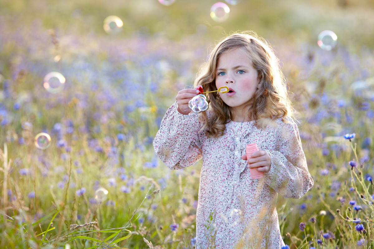 Child blowing bubbles in field full of flowers