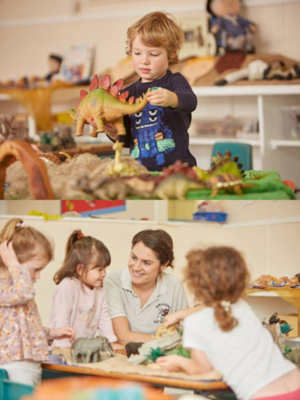 Children in preschool playing with dinosaur toys with teacher
