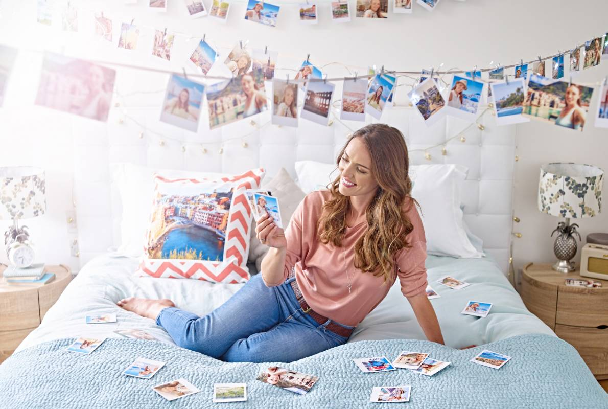 relaxed lady looking at polaroid photographs in bedroom