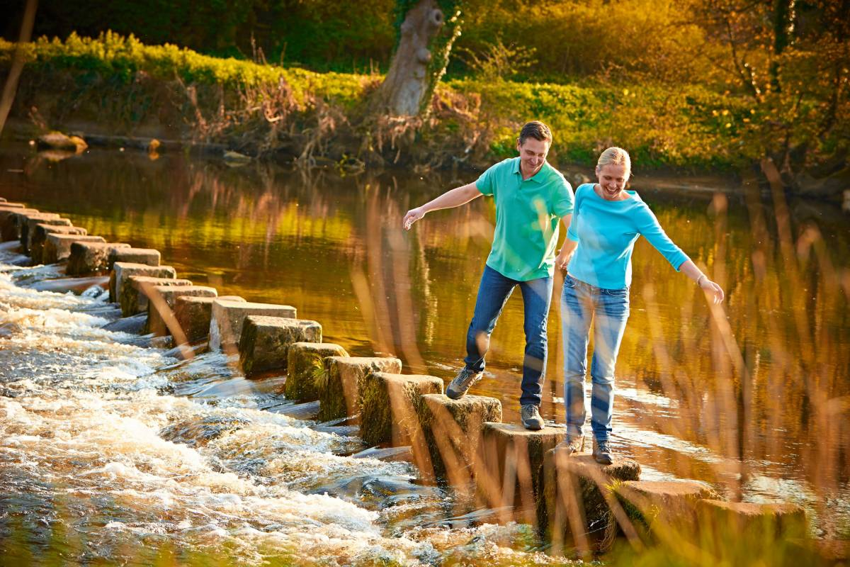 couple walking hand-in-hand across river stepping stones