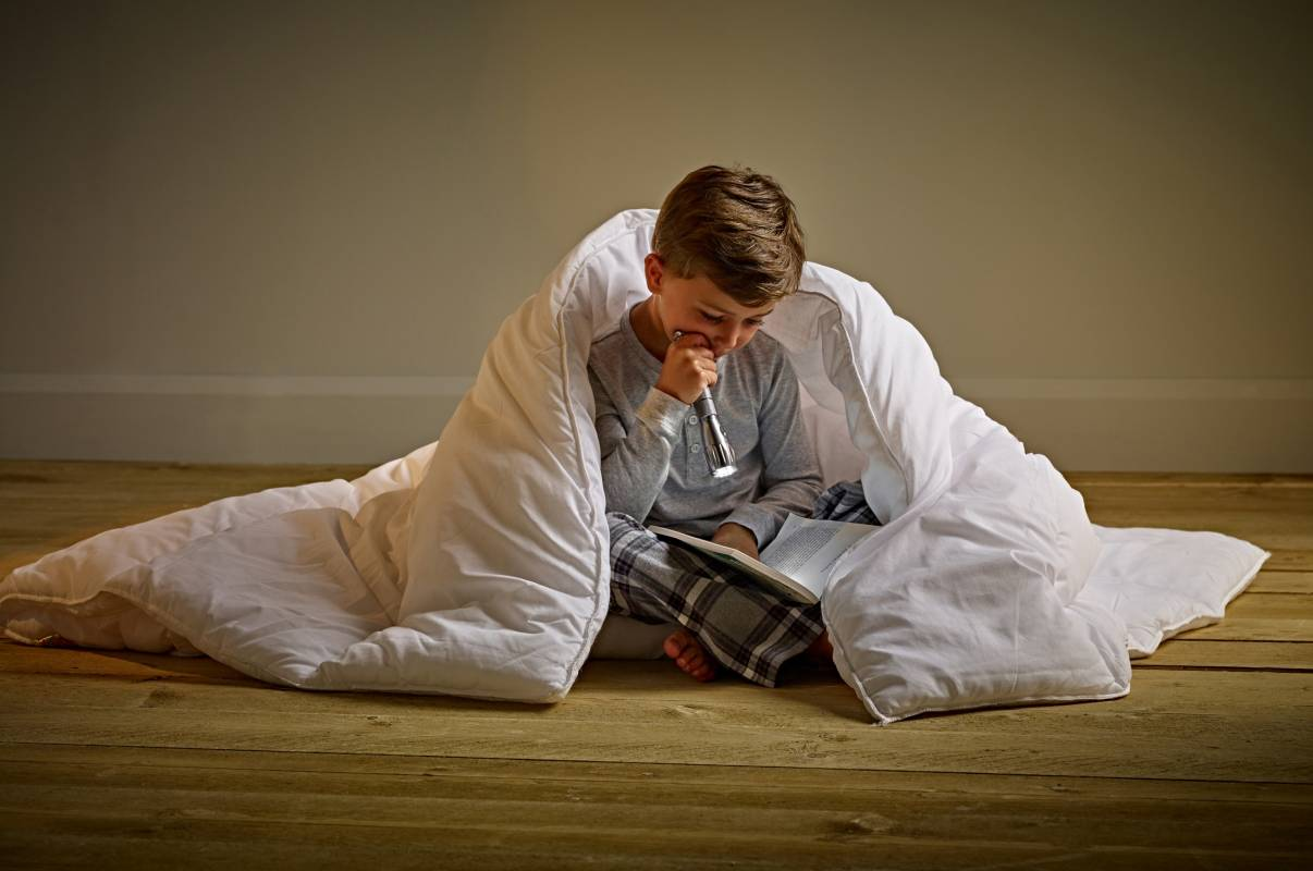 Boy reading with torch under duvet
