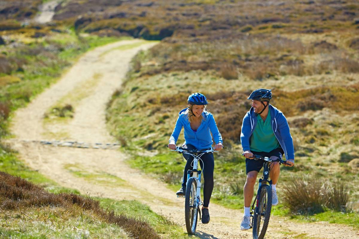 Couple cycling in yorkshire dales countryside