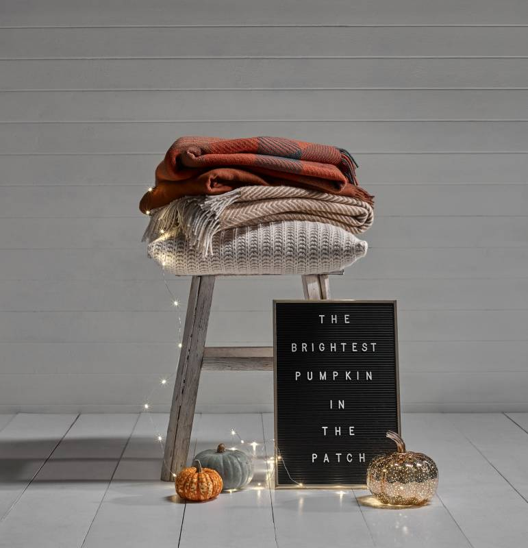 The brightest pumpkin in the patch check blankets and knitted cushion on a stool